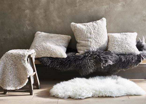 Sheepskin throws, rugs and cushions on bench